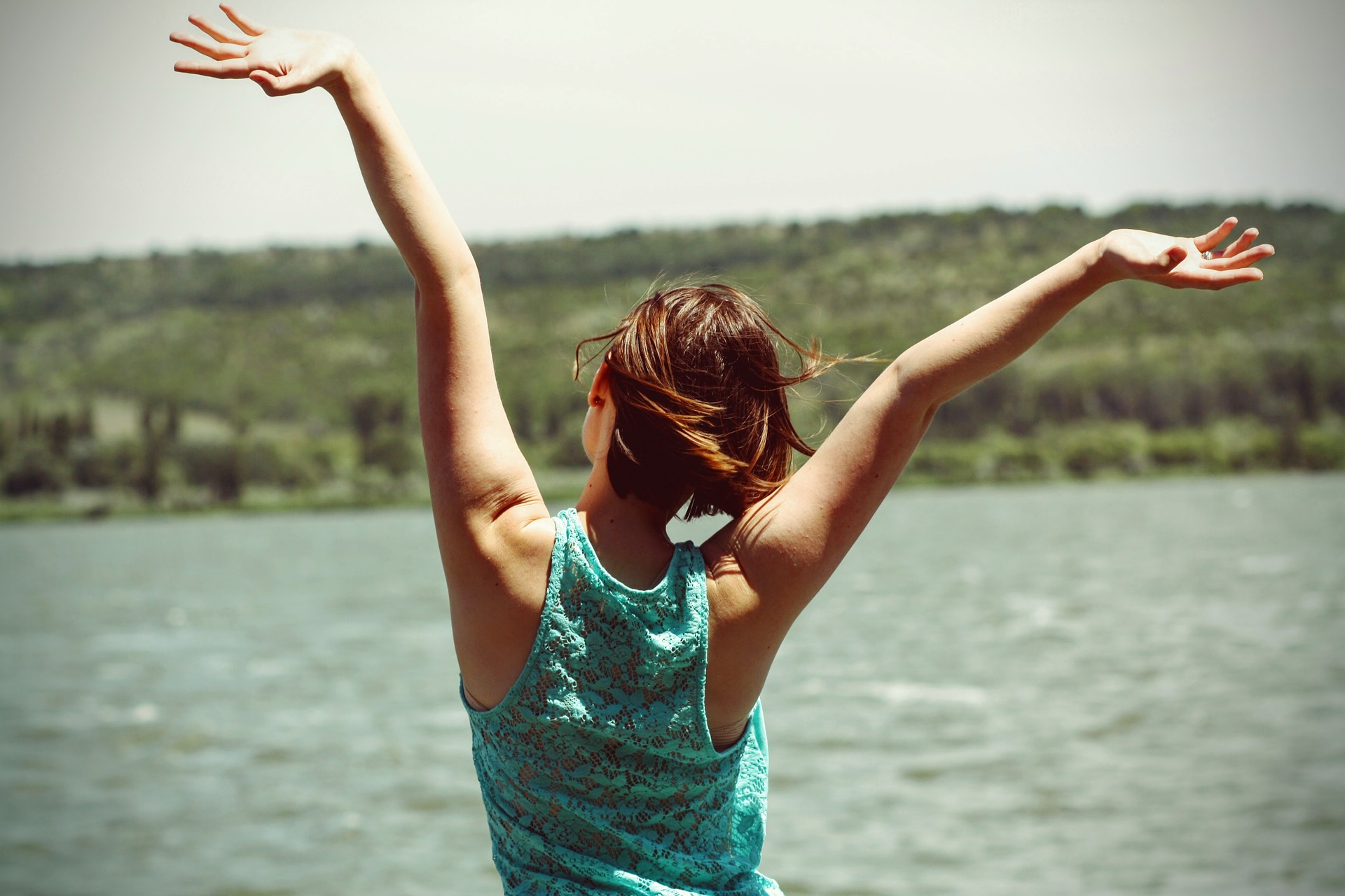 a girl in a cheerful mood standing in front of a lake with her arms stretched