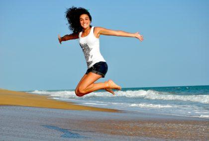 a girl jumping on a sea beach
